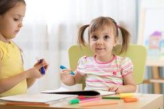 Ungar som in drar, kindergaten Barnmålarfärg i barnkammare Förskolebarn med den hemmastadda pennan Idérika små barn royaltyfri fotografi