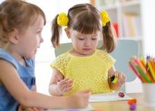 Ungar som in drar, kindergaten Barnmålarfärg i barnkammare Förskolebarn med hemmastadda blyertspennor Idérika små barn royaltyfri bild
