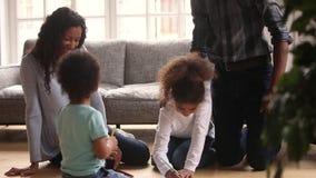 Ungar som drar spendera fri tid med föräldrar på varmt golv lager videofilmer