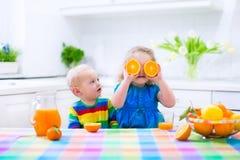 Ungar som dricker orange fruktsaft arkivfoto