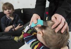 Ungar som får huvudet kontrollerat för löss Royaltyfri Fotografi