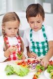 Ungar som förbereder ett grönsakmellanmål i köket Arkivbild