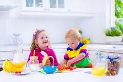 Ungar som förbereder frukosten i ett vitt kök royaltyfri fotografi