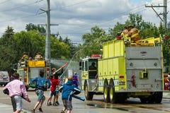Ungar som försöker att bespruta brandkämparna med vatten Royaltyfri Bild