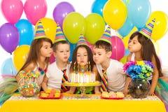 Ungar som firar partiet och att blåsa för födelsedag Arkivbild