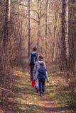 Ungar som fotvandrar till och med en skog Arkivbilder