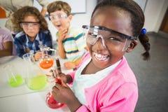 Ungar som gör ett kemiskt experiment i laboratorium arkivfoton