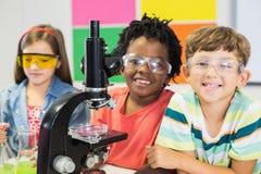 Ungar som gör experiment på mikroskopet i laboratorium royaltyfria bilder