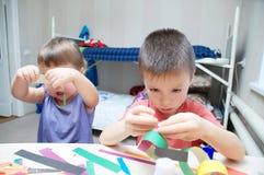 Ungar som gör papper, färgade girlanden, syskon hantverk, brodern och s fotografering för bildbyråer