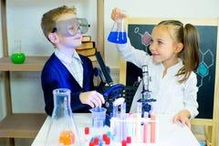 Ungar som gör vetenskapsexperiment arkivfoton
