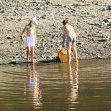 Ungar som gör ren en sjö Royaltyfri Foto