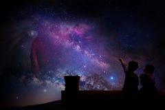 Ungar som håller ögonen på stjärnorna på taket av deras hus på natten Royaltyfria Bilder