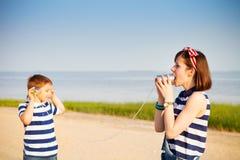 Ungar som har en påringning med tenn- cans fotografering för bildbyråer