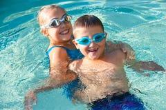 Ungar som har gyckel i simbassäng. Royaltyfri Fotografi