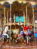 Ungar som har gyckel på en karusell Royaltyfri Bild