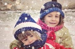 Ungar som har gyckel på en snöig vinterdag Royaltyfria Foton