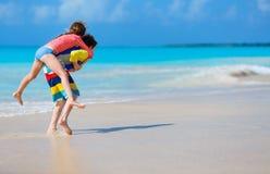 Ungar som har gyckel på stranden arkivbild