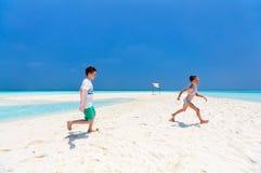 Ungar som har gyckel på stranden Arkivbilder