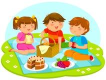 Ungar som har picknicken Arkivbild