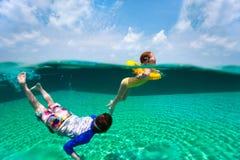 Ungar som har rolig simning på sommarsemester arkivbilder