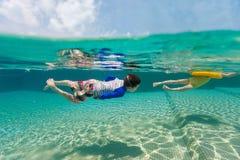 Ungar som har rolig simning på sommarsemester arkivfoto