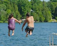 Ungar som har roligt hoppa för sommar av skeppsdocka in i sjön Arkivfoton