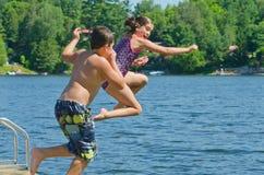 Ungar som har roligt hoppa för sommar av skeppsdocka in i sjön Arkivbild