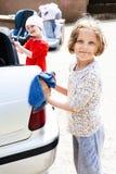 Ungar som hjälper den rena bilen Arkivbild