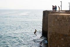 Ungar som hoppar in i havet i Akko Arkivbild