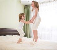Ungar som hoppar på säng Arkivfoto