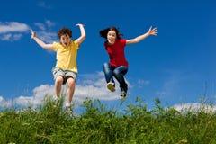 Ungar som kör, hoppa som är utomhus- Royaltyfri Foto