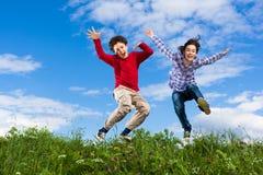 Ungar som kör, hoppa som är utomhus- Fotografering för Bildbyråer