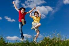 Ungar som kör, hoppa som är utomhus- Royaltyfria Foton