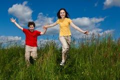 Ungar som kör, hoppa som är utomhus- Arkivbilder