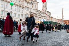 Ungar som kör i gata med ängelklänningen i rome Royaltyfri Foto
