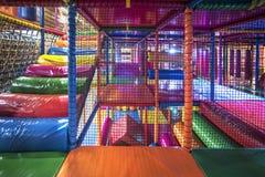 Ungar som kör inom en färgrik inomhus lekplats Arkivfoto