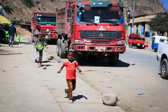 Ungar som kör nära enorma lastbilar, som stoppade förbi för, vilar arkivbild