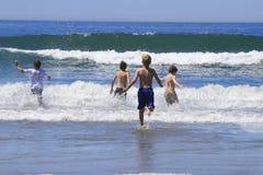 ungar som kör waves Arkivbild