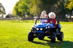 Ungar som k?r den elektriska leksakbilen utomhus- toys royaltyfri bild