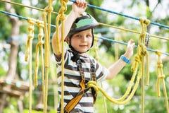 Ungar som klättrar i affärsföretag, parkerar Pojken tycker om att klättra i repet Royaltyfria Foton