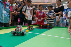 Ungar som kontrollerar robotar i en robotfotbollsmatch Royaltyfria Foton