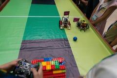 Ungar som kontrollerar robotar i en robotfotbollsmatch Royaltyfria Bilder