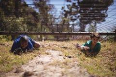 Ungar som kryper under det netto under hinderkurs royaltyfri fotografi