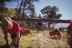 Ungar som kryper under det netto under utbildning för hinderkurs fotografering för bildbyråer