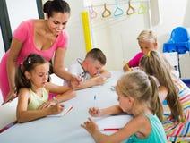 Ungar som lär att skriva på kurs i grundskolagrupp royaltyfri bild
