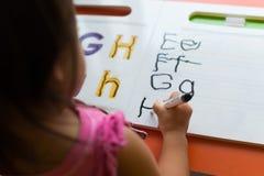 Ungar som lär hur man skriver de hemmastadda abc'sna royaltyfri foto