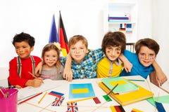 Ungar som lär språk som sitter i linje på ett skrivbord Arkivfoton