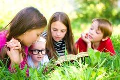 Ungar som läser en bok Royaltyfri Bild