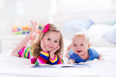 Ungar som läser i det vita sovrummet Arkivfoto