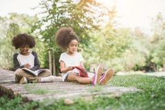 Ungar som läser med vännen Royaltyfria Bilder